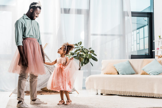 happy african american father looking at cute daughter in beautiful dress