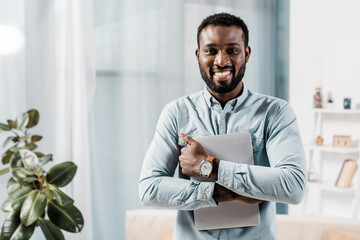 african american freelancer smiling with laptop in hands