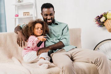 african american man and daughter watching TV together in living room