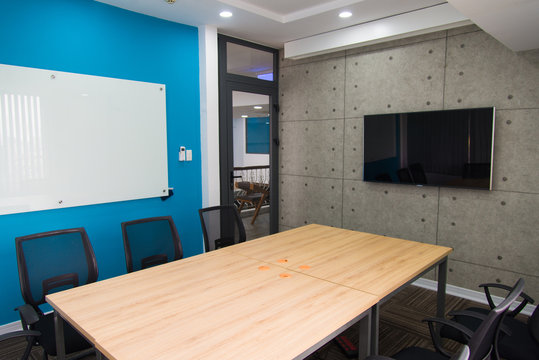 Conference room with television set and whiteboard on walls. Wooden table and chairs in center of urban design meeting room. Office concept