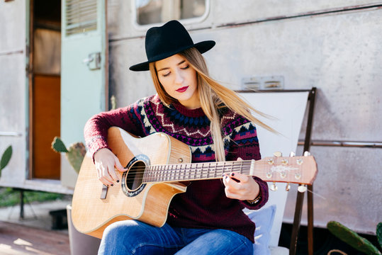 Young woman playing guitar near caravan