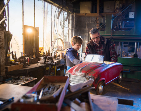 Father and his young son in a DIY workshop to repair a pedal car