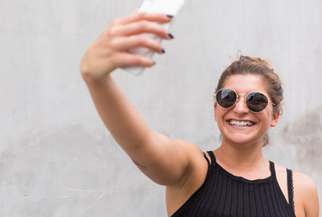 Portrait of laughing young woman wearing sunglasses taking selfie with smartphone