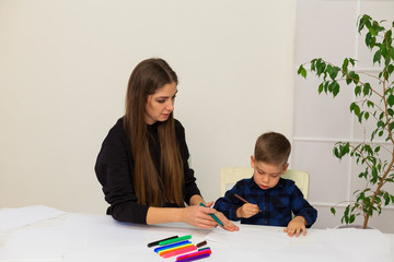 little boy draws markers from lesson mother