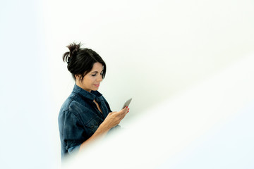 Dark-haired woman wearing denim shirt looking at cell phone