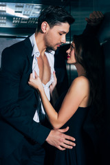 beautiful woman passionately undressing and embracing handsome man in elevator