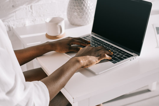 cropped view of african american woman using laptop with blank screen