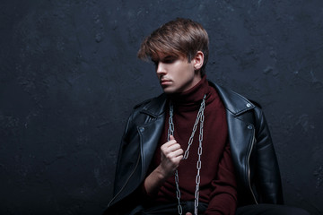 A young attractive man in a leather jacket in warm burgundy golf with a metallic silver chain around his neck, posing in a dark studio against a black wall. Cute fashion guy