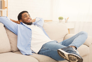 Handsome african-ameriacn man relaxing on sofa at home