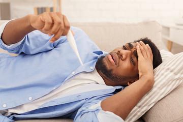 Sick black man checking his temperature at home