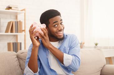 Happy black man with piggybank at home