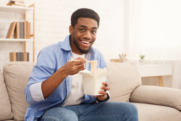 Young black man eating noodles at home