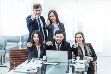 concept of success in business: professional business team near the workplace with your fingers pointing forward.