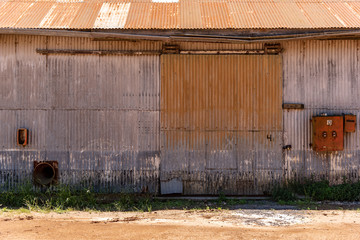 Metallic barn or deposit sliding door on silver color with an old electricity box