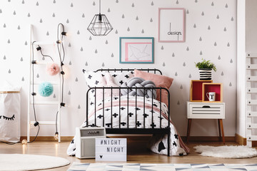 White wooden ladder with pompons and lights next to industrial bed with black and white bedding and grey knot pillow
