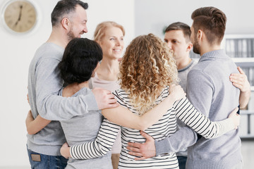 Men and women hugging each other during therapy for couples with problems