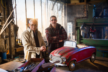 A senior man and his son at workshop to restore an old pedal car