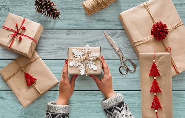 Woman's hands holding christmas holiday present decorated with snowflake