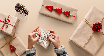 Woman's hands wrapping christmas holiday present with craft twin