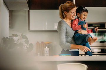 Mother and son enjoying while baking cookies in kitchen
