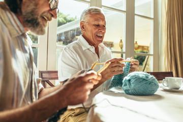 Senior friends enjoying knitting at home Wall mural