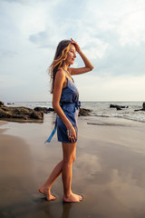 Sexy beauty brunette woman with tan skin wear grey silk dress evening makeup cosmetic summer collection clothes for strong and independent female person posing on paradise beach rocks and sand