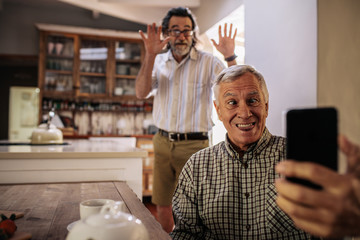 Funny seniors taking selfie at home