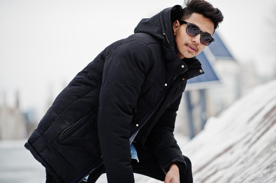 Casual young indian man in black jacket and sunglasses posed at winter day.