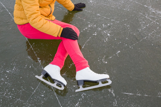 Young woman fallen on frozen lake during ice skating time in winter day. Hand in glove touching painful knee. Sporty problem and solution. Top view.