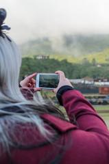 jovem de costas fotografando com celular, cidade de Paranapiacaba em São Paulo, em cores, em alta resolução, uma pessoa,