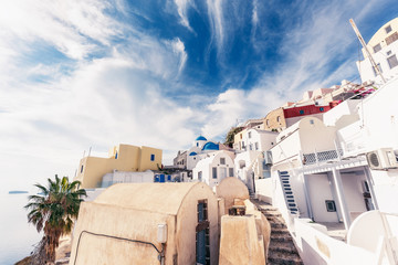 Wall Mural - Famous churches in Oia village, Santorini island in Greece, on a sunny day with dramatic sky. Scenic travel background.