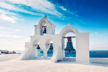 Church bells in Oia village, Santorini island in Greece, on a sunny day with dramatic sky. Scenic travel background.
