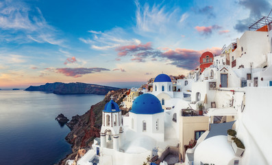 Wall Mural - Beautiful view of Oia village on Santorini island in Greece at sunrise with dramatic sky.