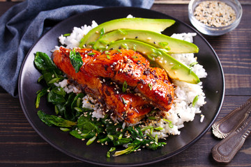 Salmon in honey-soy glaze with rice, spinach and avocado. horizontal