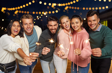 leisure, celebration and people concept - happy friends with sparklers at rooftop party at night with blurred bokeh lights