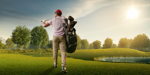 Male golf player on professional golf course. Golfer walking on fairway with golf bag and club. Back view