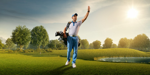 Male golf player on professional golf course. Smiling golfer walking on fairway with golf bag