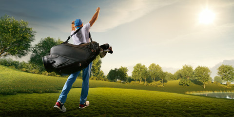 Male golf player on professional golf course. Golfer walking on fairway with golf bag. Back view