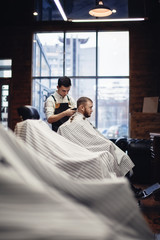 barbershop. Barber and client in the chair against the window
