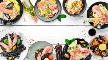 A set of seafood dishes on a white background. Pasta, bulgur, rice, couscous. Top view. Free space for your text.