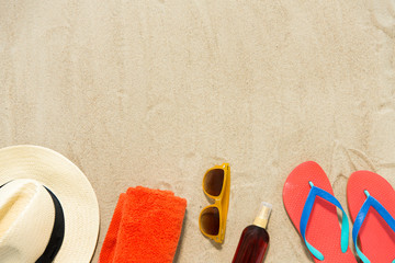 vacation, travel and summer holidays concept - straw hat, flip flops, sunglasses and sunscreen oil with seashells on beach sand Wall mural