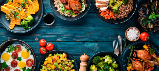 Assortment of food. Salad, avocado, quail, mushrooms, pumpkin. On a blue wooden background. Top view. Free space for your text.