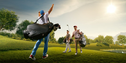 Three male golf players on professional golf course. Smiling golfers walking with golf clubs and golf bags