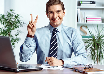Successful businessman showing victory sign. Photo of young man working in the office. Business concept