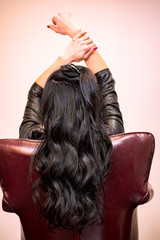 A girl with long black curly hair sits in a chair