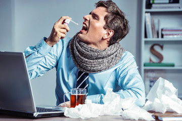 Sick employee using spray for throat. Photo of young man in office suffering virus of flu. Medical concept.