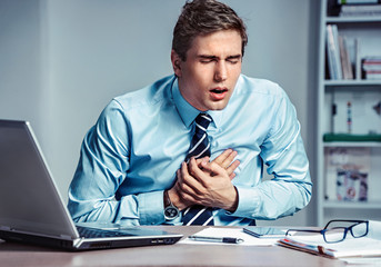 Office manager having heart attack. Photo of young man holding hand on painful chest in the workplace. Medical concept.