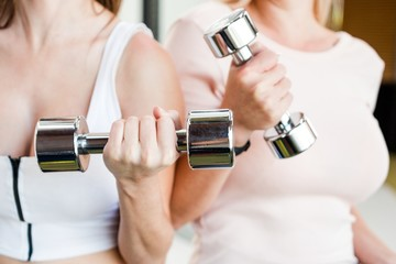 Two beautiful girls are training in the gym holding a kettlebell close-up