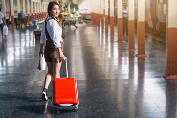 Asian woman pregnant travel carrying her trolley red bag and map in railway station travel.