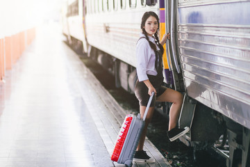 Asian woman pregnant travelers are taking a train with carrying her trolley red bag at the railway station travel.